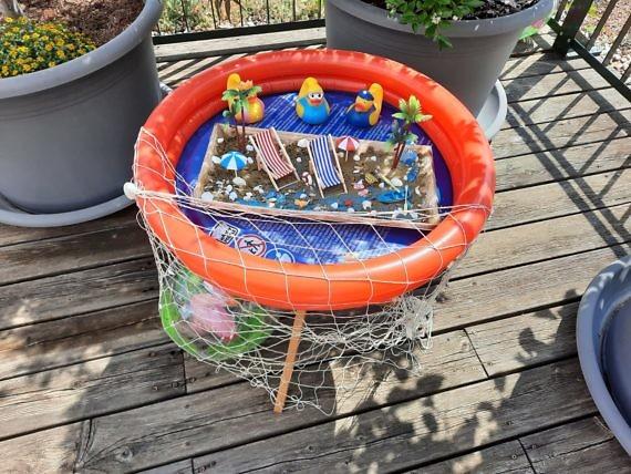 Planschbecken aus Plastik mit schwimmenden Figuren und einem übergeworfenem Netz