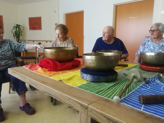 Ältere Personen auf einem schön gedeckten Tisch mit zwei Klangschalen